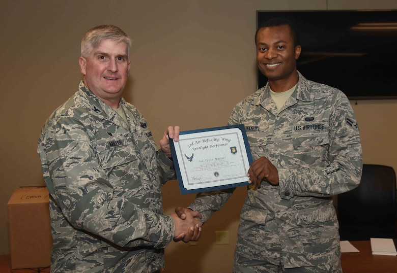 Airman 1st Class Tevin Manuel, 22nd Communications Squadron cyber surety technician, receives a certificate from Col. Albert Miller, 22nd Air Refueling Wing commander, May 18, 2017, at McConnell Air Force Base, Kan. Manuel earned the spotlight performer for the week of April 24-28. (U.S. Air Force photo/Airman 1st Class Erin McClellan)