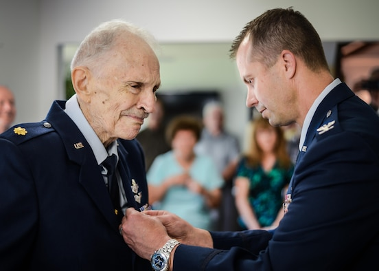 Retired Maj. Joe Campbell is awarded the Distinguished Flying Cross by Col. Ty Neuman, 2nd Bomb Wing commander, during an award ceremony at his residence in Shreveport, La., May 18, 2017. Campbell, a veteran of World War II, the Korean War, and Vietnam, received the award for heroism and extraordinary achievement during aerial operations in the Korean War. (U.S. Air Force photo/Senior Airman Mozer O. Da Cunha)