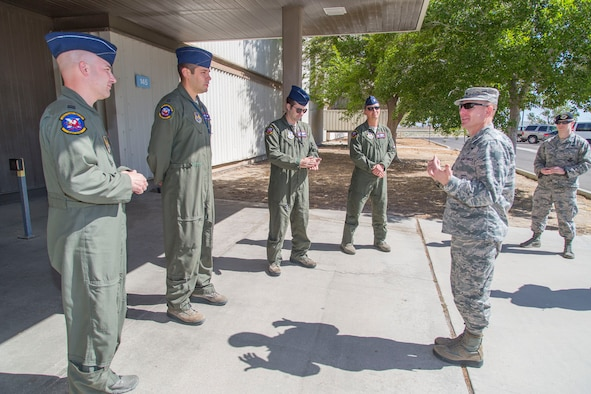 Capt. Stephen Gray (from left), Capt. James McDonald, Maj. Josh Strafaccia and Lt. Col. Miles T. Middleton, speak with Brig. Gen. Carl Schaefer (far right), 412th Test Wing commander, after he  presented challenge coins on behalf of Gen. Ellen M. Pawlikowski, commander of Air Force Materiel Command. Pawlikowski issued the coins as a thanks for efforts undertaken to make her flight possible aboard a B-52 Stratofortress during a sortie earlier this month. The bomber and crew are from the 419th Flight Test Squadron. (U.S. Air Force photo/Christopher Okula)