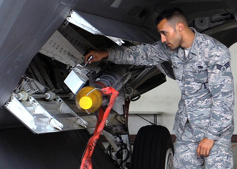 U.S. Air Force Senior Airman Christopher Lewis, 1st Maintenance Group weapons standardization lead crew member, finishes loading an AIM-9X missile onto an F-22 Raptor, at Joint Base Langley-Eustis, Va., April 19, 2017. The AIM-9X is a newer, more versatile weapon that was recently made compatible with the F-22. (U.S. Air Force photo/Airman 1st Class Amanda Dole)