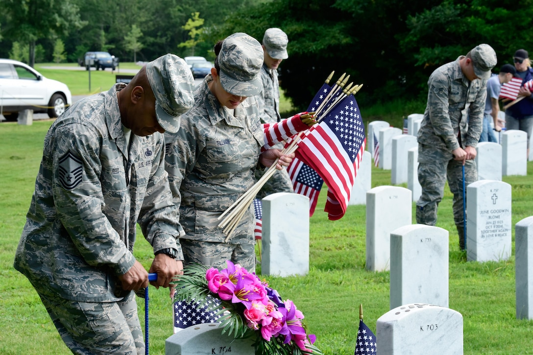 Airmen place flags near headstones at the Arkansas State Veterans Cemetery