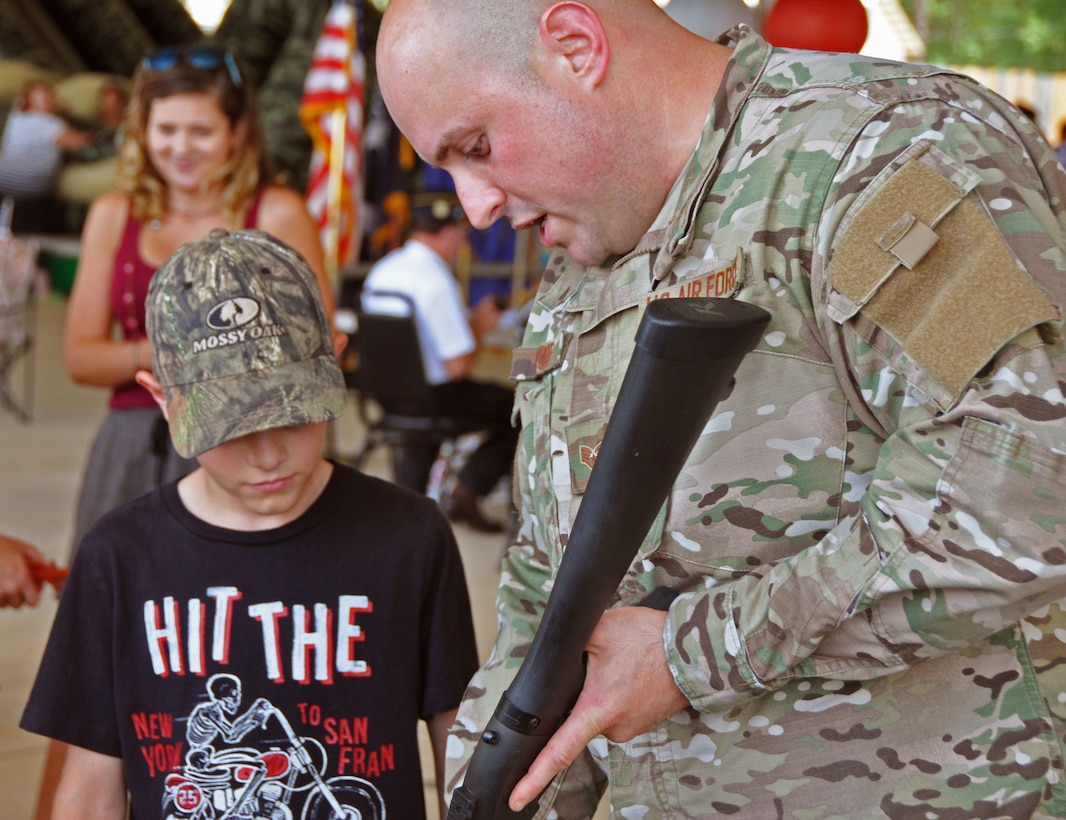 Staff Sgt. Brian Ploof, 919th Special Operations Security Forces Squadron, educates a young visitor about the M-870 shotgun at the Military Appreciation Recognition Celebration in Crestview, Fla., May 20, 2017. The annual event affords a unique opportunity for Crestview area citizens to meet military members and thank them for their service in national defense. (U.S. Air Force photo/Dan Neely)
