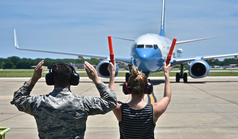 Airman 1st Class Zachary Keeven, 932nd Airlift Wing crew chief, assists Lauren Lauer with hand signals as she marshals in Maj. Jonathan Lauer on his fini flight May 22, 2017, Scott Air Force Base, Illinois.  Lauer, former executive officer for the 932nd Airlift Wing commander, took a new senior executive position with Air Mobility Command. (U.S. Air Force photo by Christopher Parr)