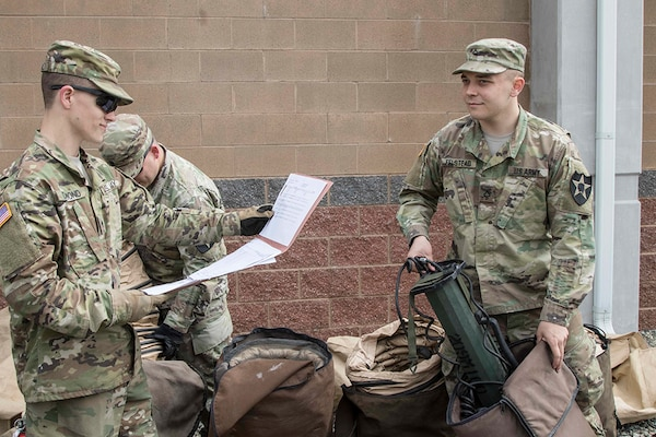 Spc. Aaron Dumond (left), a team leader with D Company, 23rd Brigade Engineer Battalion, 1-2 Stryker Brigade Combat Team, reads off a list of required items needed for turning in their Deployable Rapid Assembly Shelter.