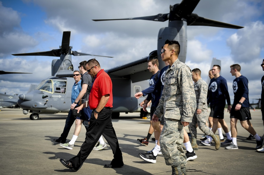 Members of the Air Force volleyball team walk to a CV-22 Osprey tilt-rotor aircraft static display during a tour at Hurlburt Field, Fla., May 11, 2017. Out of more than 50 applicants, 18 Airmen tried out and 12 Airmen made the team for the 2017 season. (U.S. Air Force photo by Airman 1st Class Dennis Spain)
