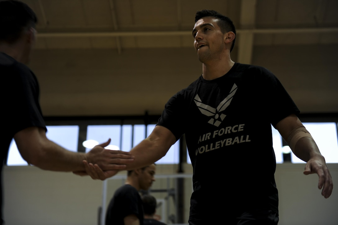 1st Lt. Kevin Plascencia, a middle blocker with the Air Force men's volleyball team, shakes hands with a teammate during practice at Hurlburt Field, Fla., May 23, 2017. Plascencia, assigned to Air Force Life Cycle Management Center at Hanscom Air Force Base, Mass., was one of 12 selected from 50 applicants for the 2017 season. (U.S. Air Force photo by Airman 1st Class Dennis Spain)