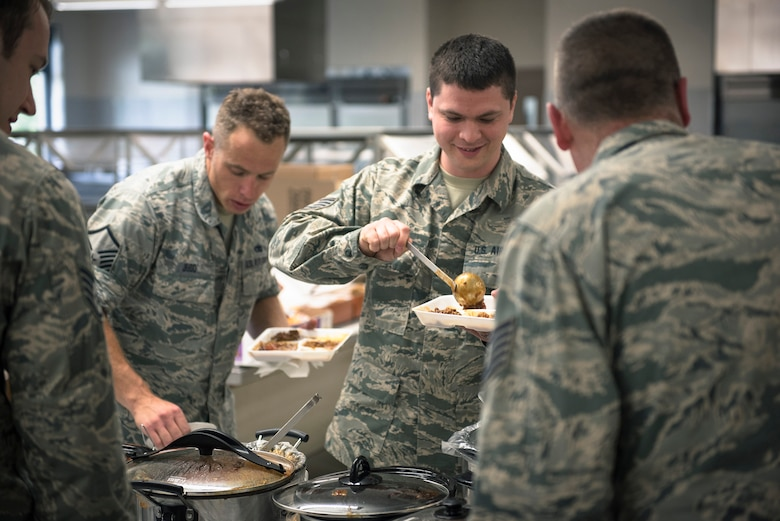 Airmen with the 182nd Airlift Wing, Illinois Air National Guard, scoop chili onto their plates at the wing's ninth-annual chili cook-off in Peoria, Ill., May 17, 2017. Staff Sgt. Nicholas Freeman, an aerospace maintenance journeyman with the 182nd Aircraft Maintenance Squadron, Illinois Air National Guard, won first place in overall points, first place for consistency and tied for second place in the People's Choice vote against 13 other chilies. (U.S. Air National Guard photo by Tech. Sgt. Lealan Buehrer)
