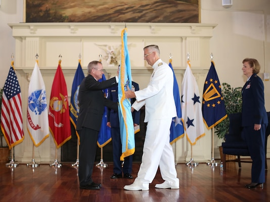 Navy Vice Adm. David H. Lewis receives the Defense Contract Management Agency flag from James MacStravic, performing the duties of  undersecretary of defense for acquisition, technology and logistics, at a May 24 change of command ceremony at Fort Lee, Virginia. Lewis relieves Air Force Lt. Gen. Wendy Masiello as director of Fort Lee-headquartered DCMA and its 12,000 acquisition professionals working out of offices and production