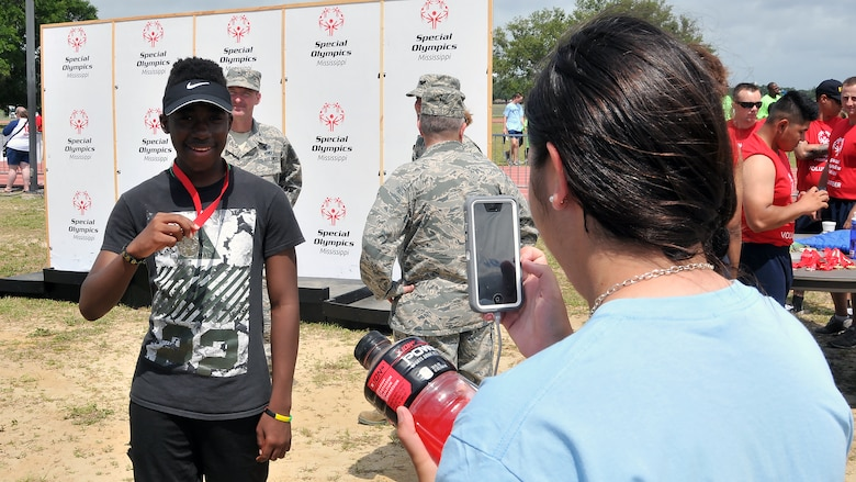 Airman 1st Class Sierra Ward, 335th Training Squadron personnel student, takes a picture of Nicholas Berry, a Special Olympics athlete, during the Special Olympics Mississippi 2017 Summer Games May 20, 2017, on Keesler Air Force Base, Miss. Berry earned a gold medal in the standing long jump event and a silver medal in the 200-meter dash. (U.S. Air Force photo by Senior Airman Jenay Randolph)