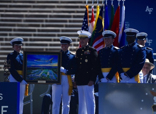 Chairman of the the Joint Chiefs of Staff Marine Gen. Joseph Dunford (center) stands between newly-minted second lieutenants May 24, 2017, after giving the commencement speech for the U.S. Air Force Academy's graduating Class of 2017. The new Air Force officers (left) hold a painting presented to the chairman by the Class of 2017. (U.S. Air Force photo/Tech. Sgt. Julius Delos Reyes)