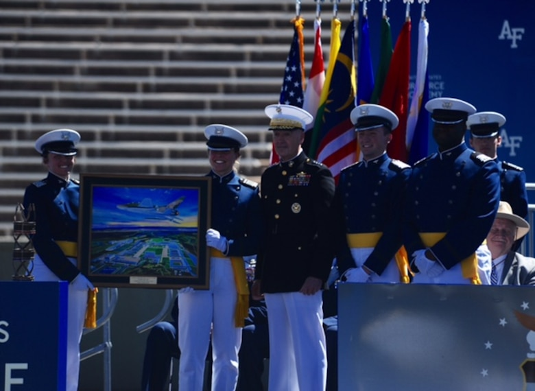 Chairman of the the Joint Chiefs of Staff Marine Gen. Joseph Dunford (center) stands between newly-minted second lieutenants after giving the commencement speech for the U.S. Air Force Academy's graduating Class of 2017. The new Air Force officers (left) hold a painting presented to the chairman by the Class of 2017. (U.S. Air Force photo/Tech. Sgt. Julius Delos Reyes)
