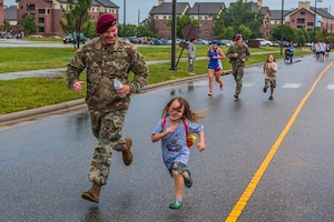 A paratrooper runs with a child during a family fun run as part of All American Week at Fort Bragg, N.C., May 23, 2017. The week celebrates the 82nd Airborne Division with events for soldiers, veterans and families. Army photo by Spc. L'Erin Wynn