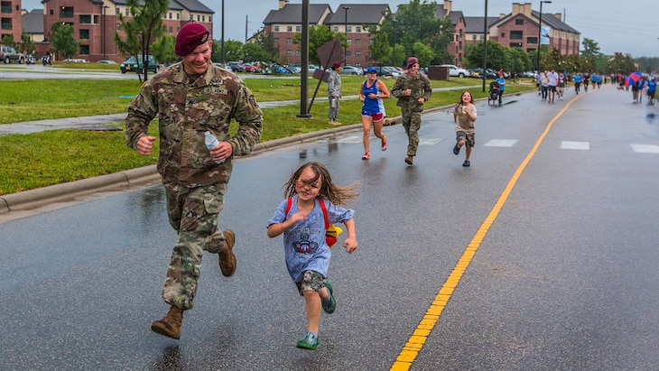 A paratrooper runs with a child during an All American Week family fun run at Fort Bragg, N.C., May 23, 2017. The week celebrates the 82nd Airborne Division with events for soldiers, veterans and families. Army photo by Spc. L'Erin Wynn