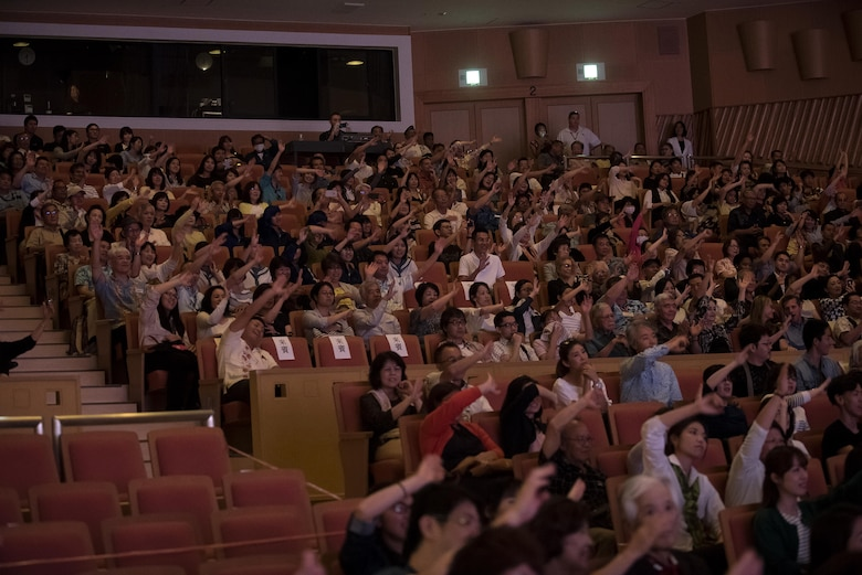 Okinawan spectators wave their arms to the music at the U.S. Air Force Band of the Pacific-Asia, Pacific Trends concert at Tedako Hall in Urazoe City, Japan, May 24, 2017. Audience members enjoyed two hours of the Pacific Trends' covers of popular American and Japanese rock songs. (U.S. Air Force photo by Senior Airman Corey Pettis)