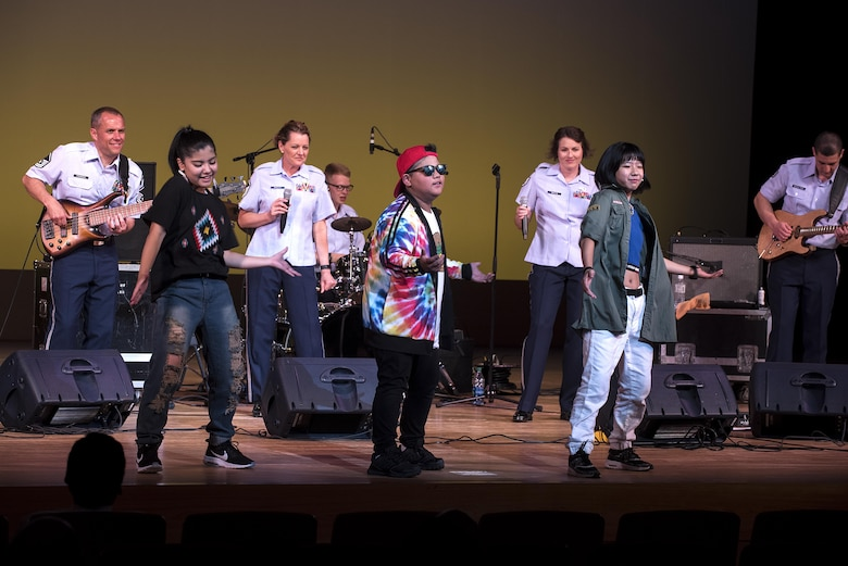 "Okinawan jr. high school students dance on stage with members of the U.S. Air Force Band of the Pacific-Asia at the Pacific Trends concert in Tedako Hall in Urazoe City, Japan, May 24, 2017. The students performed a choreographed routine as the band played the song ""Happy."" (U.S. Air Force photo by Senior Airman Corey Pettis)"