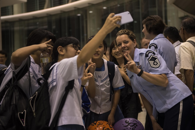 U.S. Air Force Master Sgt. Julie Bradley, U.S. Air Force Band of the Pacific-Asia, Pacific Trends singer, takes a picture with fans after a concert at Tedako Hall in Urazoe City, Japan, May 24, 2017. After performing two hours' worth of popular American and Japanese rock songs, the band members met and took pictures with audience members. (U.S. Air Force photo by Senior Airman Corey Pettis)