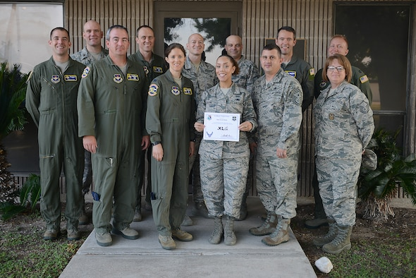 "Staff Sgt. Sarah Hahn, 47th Inspector General equal opportunity NCO in charge (center), accepts the ""XLer of the Week"" award from Col. Michelle Pryor, 47th Flying Training Wing vice commander (left), and Chief Master Sgt. George Richey, 47th FTW command chief (right), on Laughlin Air Force Base, Texas, May 17, 2017. The XLer is a weekly award chosen by wing leadership and is presented to those who consistently make outstanding contributions to their unit and Laughlin. (U.S. Air Force photo/Airman 1st Class Benjamin N. Valmoja)"