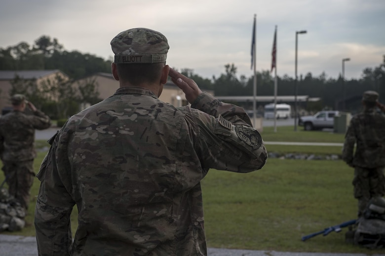 Staff Sgt. Christopher Elliot, 822nd Base Defense Squadron fire team leader, salutes during reveille before completing the last task for an Army Air Assault assessment, May 19, 2017, at Moody Air Force Base, Ga. Twenty-six Airmen attended the assessment which measured candidates' aptitude in Air Assault operations, completion of equipment layouts, and rappelling. (U.S. Air Force photo by Tech. Sgt. Zachary Wolf)