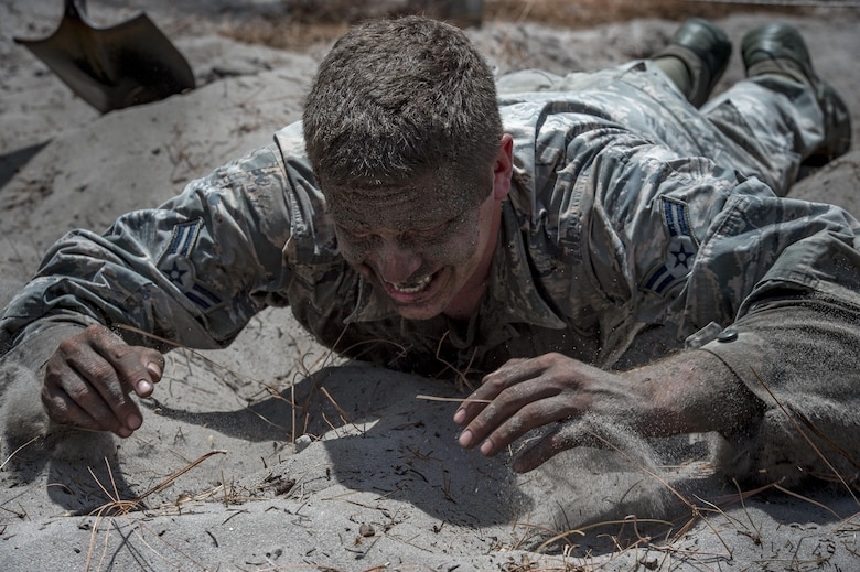 Airman 1st Class Daniel Snider, 23d Wing Public Affairs photojournalist, pulls himself through a low-crawl obstacle during an Army Air Assault assessment, May 18, 2017, at Camp Blanding, Fla. Twenty-six Airmen attended the assessment which measured candidates' aptitude in Air Assault operations, completion of equipment layouts, and rappelling. (U.S. Air Force photo by Tech. Sgt. Zachary Wolf)
