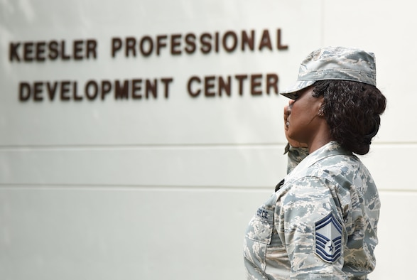 Senior Master Sgt. Tiffany Patterson, 81st Force Support Squadron career assistance advisor, renders a salute during the national anthem at the Professional Development Center's grand reopening and ribbon cutting ceremony May 17, 2017, on Keesler Air Force Base, Miss. The renovated facility offers developmental opportunities and various courses that fit the needs of officers, enlisted, civilians and reservists. (U.S. Air Force photo by Kemberly Groue)