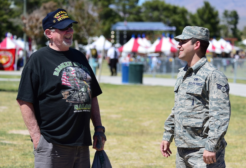 An MQ-1 Predator maintainer shares a laugh with a Vietnam veteran during the American Patriot Festival May 20, 2017, in Las Vegas. Veterans and their families gathered around the MQ-1 to ask questions and learn about the aircraft and its capabilities. (U.S. Air Force photo/Senior Airman Christian Clausen)