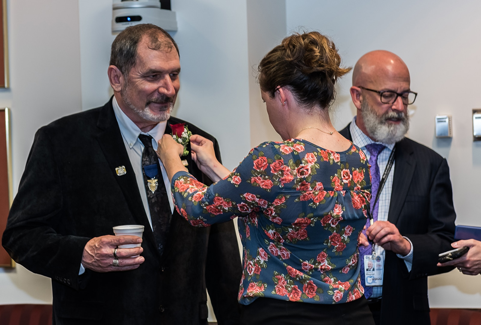 Michael Souders gets a flower pinned on by Protocol Officer Kristin Molinaro before the 2017 DLA Land and Maritime Hall of Fame induction ceremony begins.