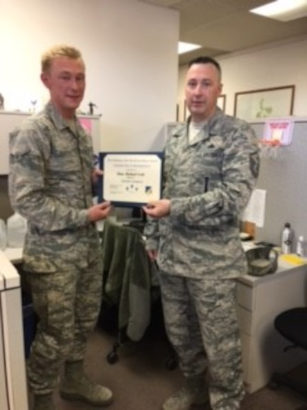 Airman Michael Scott, 49th Civil Engineer Squadron construction apprentice, is presented the Top III Airman award for April from Master Sgt. Timothy Gatten, 54th Aircraft Maintenance Squadron first sergeant and Top III President, at Holloman Air Force Base on May 24, 2017. During the month of April, Scott completed 13 surveys refining the base common installation picture and captured the placement of 1,200 feet of underground electrical conduit in direct support of a $2.4 million electrical distribution repair project.  (Courtesy photo)