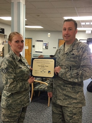 Staff Sgt. Jennifer Faria, 49th Aerospace Medical Squadron public health technician, is presented the Top III non-commissioned officer award for April from Master Sgt. Timothy Gatten, 54th Aircraft Maintenance Squadron first sergeant and Top III President, at Holloman Air Force Base on May 24, 2017. During the month of April, Faria inspected 25 food and public facilities, identified 20 discrepancies that required attention, essentially protecting approximately 18 thousand people from foodborne illness outbreaks. Faria is dedicated to mentoring Airmen, and briefed the First Term Airman Center on topics including The Enlisted Force Structure and on the Airman Comprehensive Assessment. (Courtesy photo)