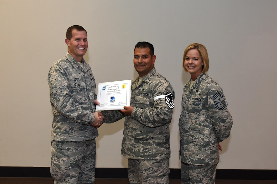 U.S. Air Force Master Sgt. select Luis Alcantar, 17th Security Forces Squadron, receives his certificate of selection from Col. Jeffrey Sorrell, 17th Training Wing vice commander, and Chief Master Sergeant Bobbie Riensche, 17th Training Wing command chief, during the Master Sergeant Release Party at the Event Center on Goodfellow Air Force Base, Texas, May 24, 2017.