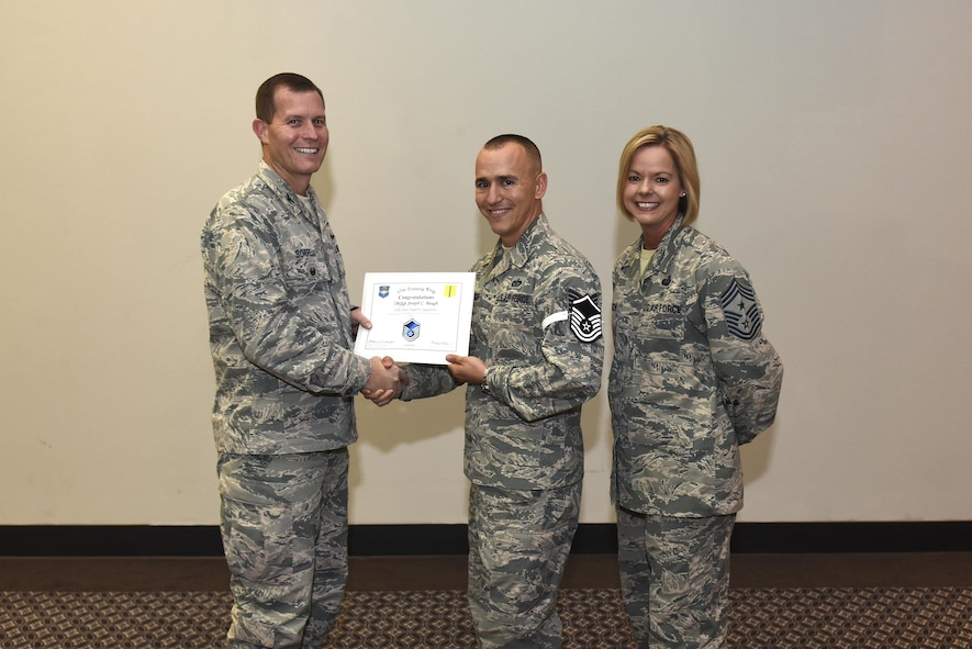 U.S. Air Force Master Sgt. select Joseph Baugh, 17th Force Support Squadron, receives his certificate of selection from Col. Jeffrey Sorrell, 17th Training Wing vice commander, and Chief Master Sergeant Bobbie Riensche, 17th Training Wing command chief, during the Master Sergeant Release Party at the Event Center on Goodfellow Air Force Base, Texas, May 24, 2017.