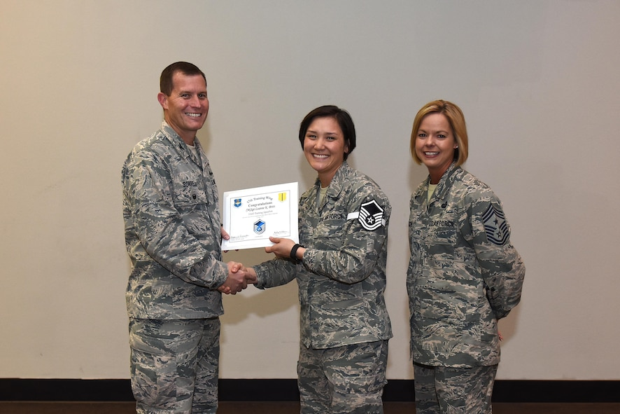 U.S. Air Force Master Sgt. select Leanne Britt, 316th Training Squadron, receives her certificate of selection from Col. Jeffrey Sorrell, 17th Training Wing vice commander, and Chief Master Sergeant Bobbie Riensche, 17th Training Wing command chief, during the Master Sergeant Release Party at the Event Center on Goodfellow Air Force Base, Texas, May 24, 2017.