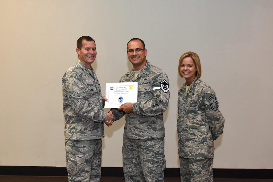U.S. Air Force Master Sgt. select Salvatore Corrao, 17th Training Support Squadron, receives his certificate of selection from Lt. Col. Jeffrey Sorrell, 17th Training Wing Vice Commander, and Chief Master Sergeant Bobbie Riensche, 17th Training Wing Command Chief, during the Master Sergeant Release Party at the Event Center on Goodfellow Air Force Base, Texas, May 24, 2017. (U.S. Air Force photo by Airman 1st Class Caelynn Ferguson/ Released)
