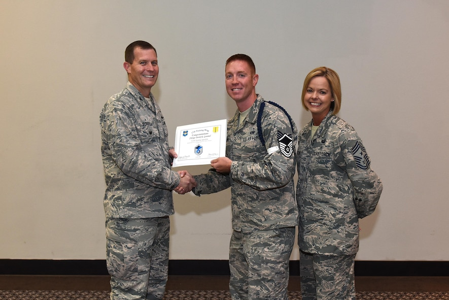 U.S. Air Force Master Sgt. select Derek Gammel, 315th Training Squadron, receives his certificate of selection from Col. Jeffrey Sorrell, 17th Training Wing vice commander, and Chief Master Sergeant Bobbie Riensche, 17th Training Wing command chief, during the Master Sergeant Release Party at the Event Center on Goodfellow Air Force Base, Texas, May 24, 2017.