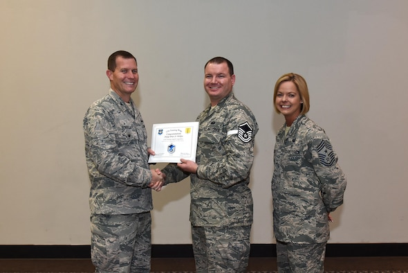 U.S. Air Force Master Sgt. select Bruce Perkins, 17th Training Support Squadron, receives his certificate of selection from Col. Jeffrey Sorrell, 17th Training Wing vice commander, and Chief Master Sergeant Bobbie Riensche, 17th Training Wing command chief, during the Master Sergeant Release Party at the Event Center on Goodfellow Air Force Base, Texas, May 24, 2017.