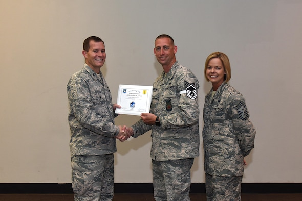 U.S. Air Force Master Sgt. select Nicholas Schnoes, 312th Training Squadron, receives his certificate of selection from Col. Jeffrey Sorrell, 17th Training Wing vice commander, and Chief Master Sergeant Bobbie Riensche, 17th Training Wing command chief, during the Master Sergeant Release Party at the Event Center on Goodfellow Air Force Base, Texas, May 24, 2017.