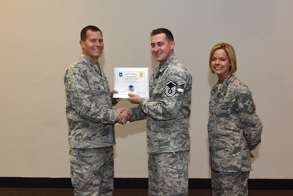 U.S. Air Force Master Sgt. select Martin Smith, 315th Training Squadron, receives his certificate of selection from Col. Jeffrey Sorrell, 17th Training Wing vice commander, and Chief Master Sergeant Bobbie Riensche, 17th Training Wing command chief, during the Master Sergeant Release Party at the Event Center on Goodfellow Air Force Base, Texas, May 24, 2017.