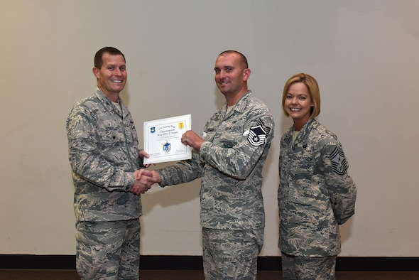 U.S. Air Force Master Sgt. select Jeffrey Trueman, 312th Training Squadron, receives his certificate of selection from Col. Jeffrey Sorrell, 17th Training Wing vice commander, and Chief Master Sergeant Bobbie Riensche, 17th Training Wing command chief, during the Master Sergeant Release Party at the Event Center on Goodfellow Air Force Base, Texas, May 24, 2017.eceives his certificate of selection from Lt. Col. Jeffrey Sorrell, 17th Training Wing Vice Commander, and Chief Master Sergeant Bobbie Riensche, 17th Training Wing Command Chief, during the Master Sergeant Release Party at the Event Center on Goodfellow Air Force Base, Texas, May 24, 2017. (U.S. Air Force photo by Airman 1st Class Caelynn Ferguson/ Released)