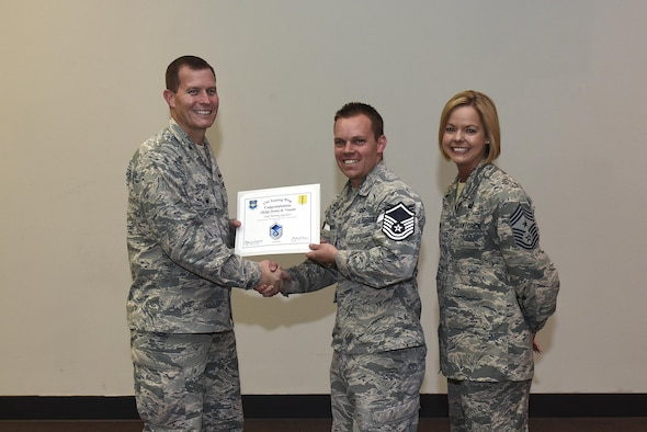 U.S. Air Force Master Sgt. select Jeremy Vonada, 316th Training Squadron, receives his certificate of selection from Col. Jeffrey Sorrell, 17th Training Wing Vice Commander, and Chief Master Sergeant Bobbie Riensche, 17th Training Wing Command Chief, during the Master Sergeant Release Party at the Event Center on Goodfellow Air Force Base, Texas, May 24, 2017. (U.S. Air Force photo by Airman 1st Class Caelynn Ferguson/ Released)
