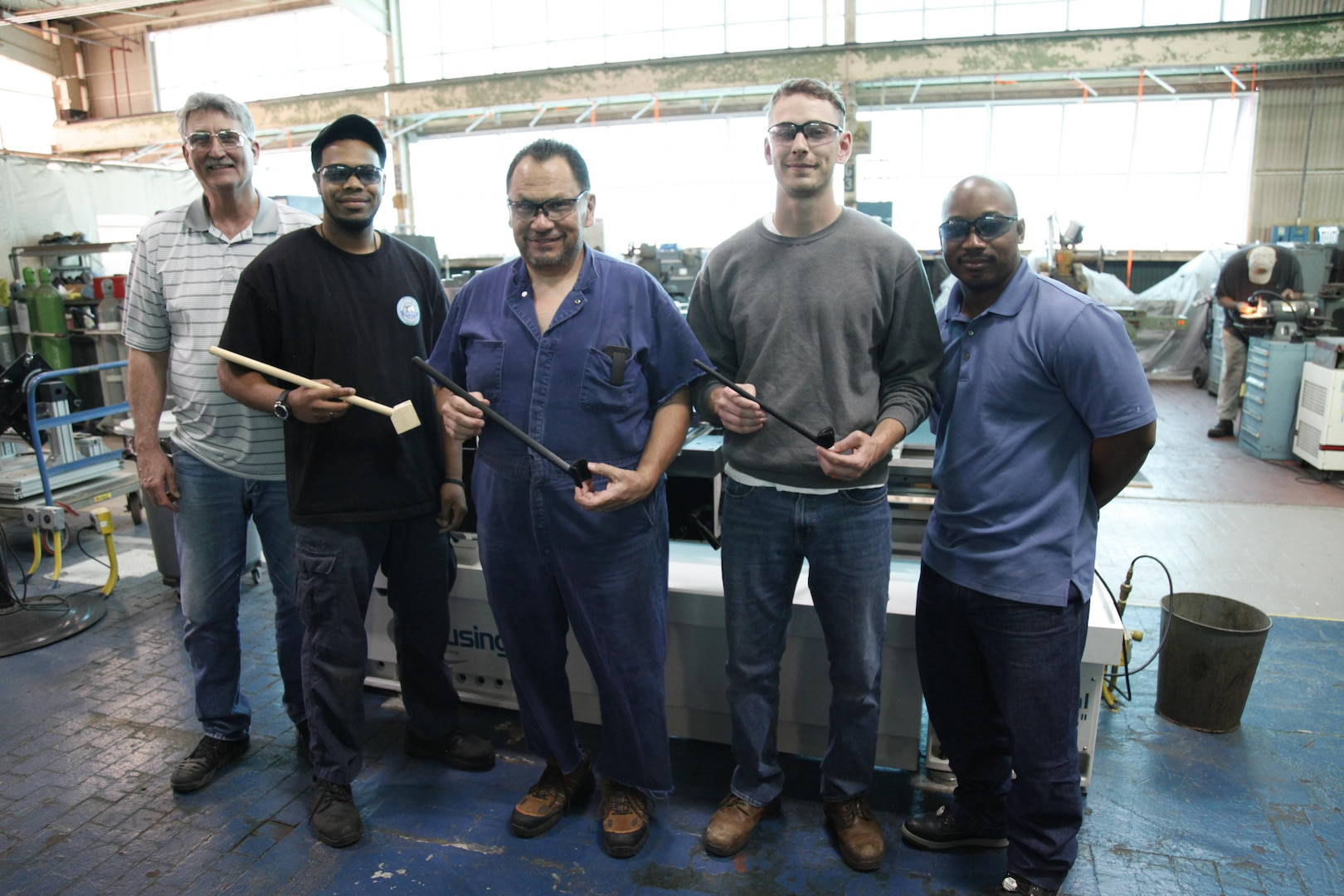 Members of the Norfolk Naval Shipyard Rapid Prototype Lab and Shop 72 (Rigging Department) Lifting and Handling Specialist Jonathan Woodruff showcase the progression of prototypes of the Tie Bolt Anti-Rotation Tool.