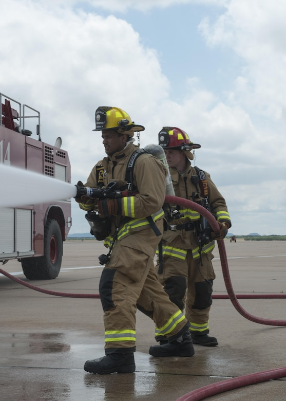 From left to right, U.S. Air Force Senior Airman Clements Dorsey, 7th Civil Engineer Squadron Fire Prevention craftsman, and Staff Sgt. Jared Weeks 7th Civil Engineering Squadron Fire Prevention crew chief, participate in a group-training exercise at Dyess Air Force Base, Texas, May 22, 2017. In addition to using water to extinguish fires, firefighters may use foam to prevent the fire from getting oxygen, resulting in the suppression of the fire. (U.S. Air Force photo by Airman 1st Class Katherine Miller)