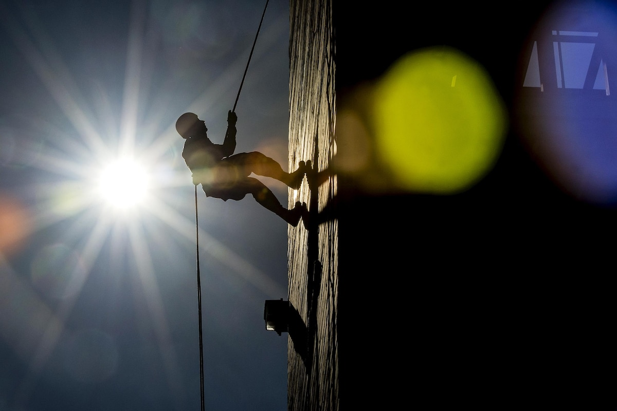 A soldier rappels down a wall at night with a bright light shining.