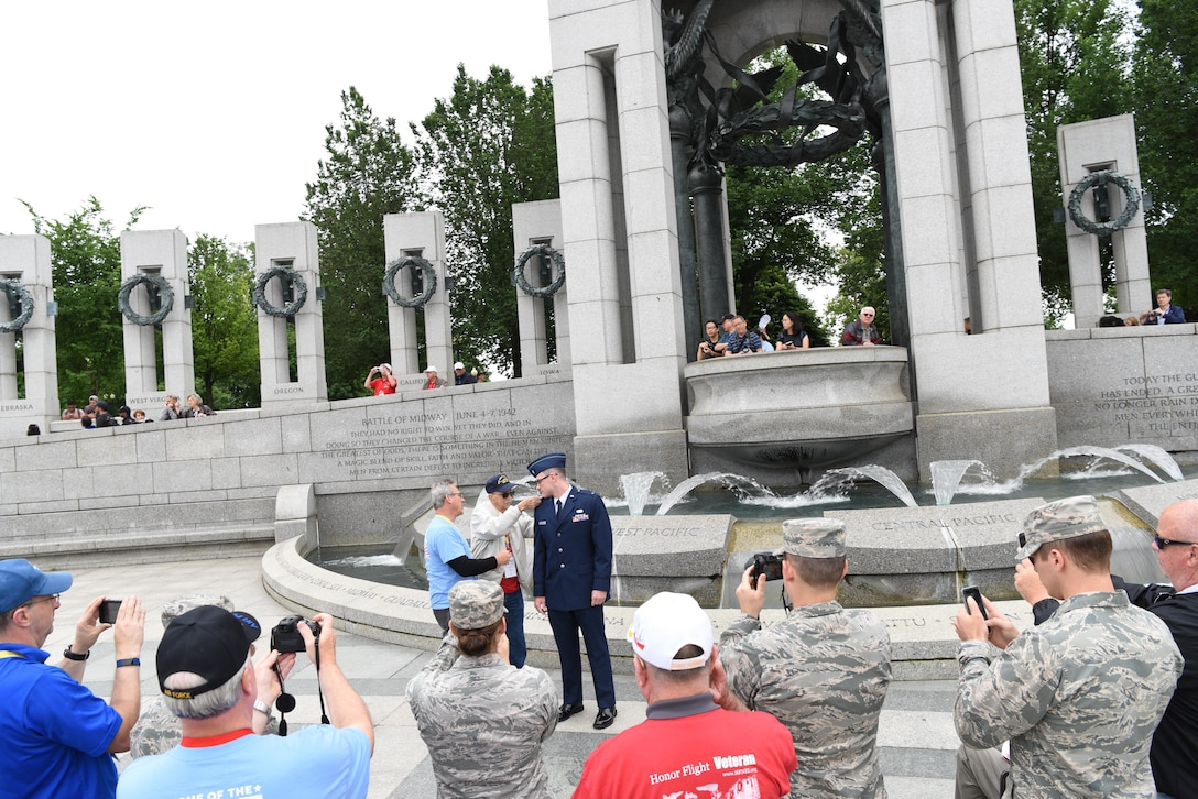 First Lt. Nicholas Lundin, 480th Intelligence, Reconnaissance and Surveillance Wing chief of current operations, has his ranks pinned on by his dad Michael Lundin and grandfather Ray Lundin during his promotion ceremony May 24, 2017 at the World War II memorial in Washington D.C. A crowd of veterans and guardians watched the ceremony and came up afterward to congratulation the new captain. (U.S. Air Force photo by Tech. Sgt. Darnell T. Cannady)