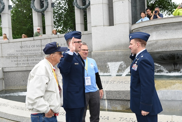 First Lt. Nicholas Lundin, 480th Intelligence, Reconnaissance and Surveillance Wing chief of current operations, stands between his dad Michael Lundin and grandfather Ray Lundin while saying the oath of enlistment administered by Lt. Col. Brian Webster, presiding officer, May 24, 2017 at the World War II memorial in Washington D.C. Underneath the Pacific portion of the World War II monument, 1st Lt. Nicholas Lundin's new rank was pinned on by his father and grandfather. (U.S. Air Force photo by Tech. Sgt. Darnell T. Cannady)