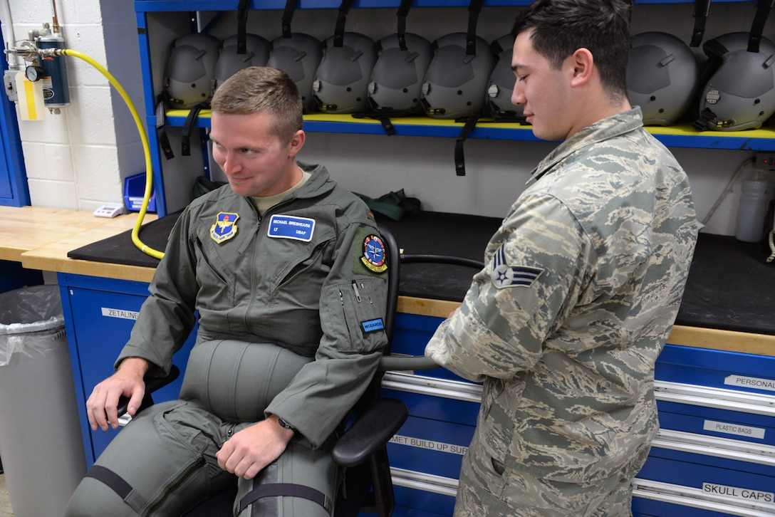 Senior Airman Carlos Garza, 80th Operations Support Squadron aircrew flight equipment technician, pushes compressed air into the G-suit of a student pilot to test the fit. Garza hand fits each suit to the individual pilot to ensure proper fit and function. (U.S. Air Force photo by Senior Airman Robert L. McIlrath)