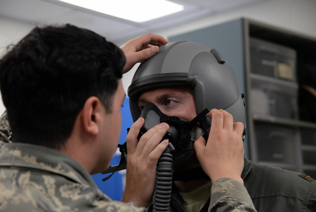 Senior Airman Carlos Garza, 80th Operations Support Squadron aircrew flight equipment technician, adjusts the helmet and mask of a student pilot to check proper fit and seal. A set of pilot equipment consists of a helmet, mask, parachute and G-suit, more than 140 sets are inspected weekly. (U.S. Air Force photo by Senior Airman Robert L. McIlrath)