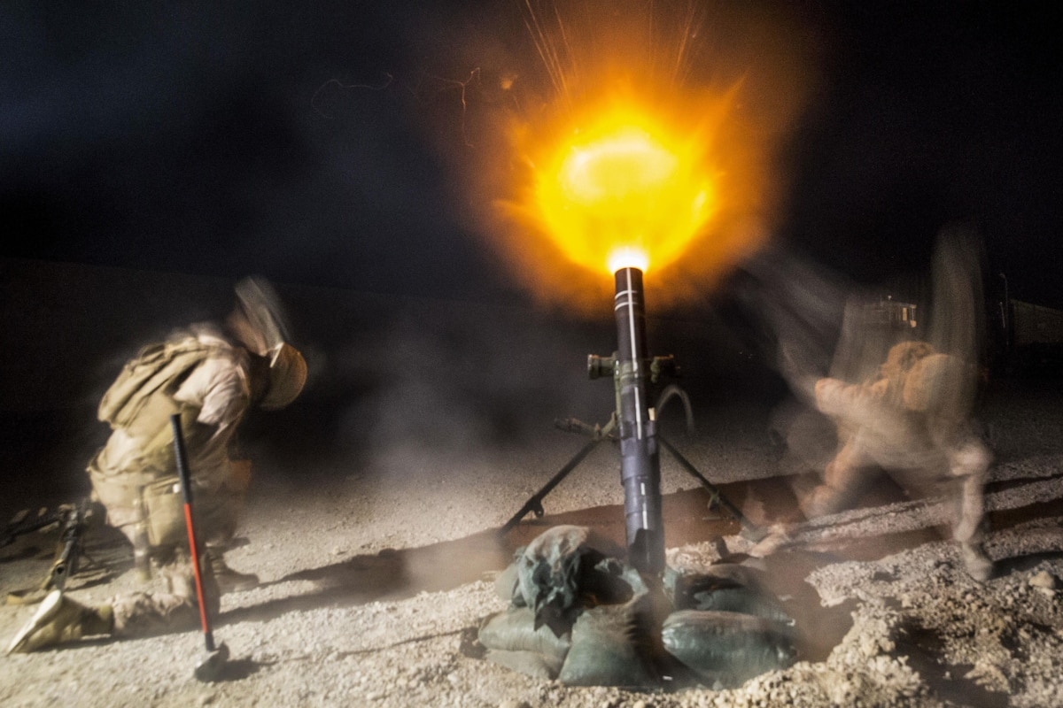 Marines fire an illumination mortar round at night on an airfield.