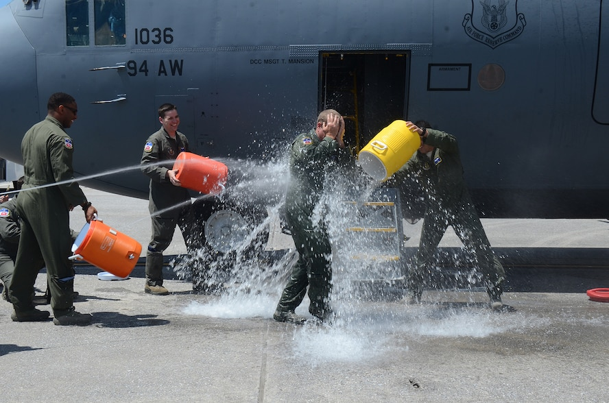 Being honored for 33 years of military service, Master Sgt. Steve Belcher, 700th Airlift Squadron loadmaster, is doused with water after his final C-130 flight at Dobbins Air Reserve Base May 25, 2017. Dating back to World War II, aircrew members have celebrated their last flights in similar fashion. Over the years, it has become an Air Force tradition for flyers. (U.S. Air Force photo/Don Peek)