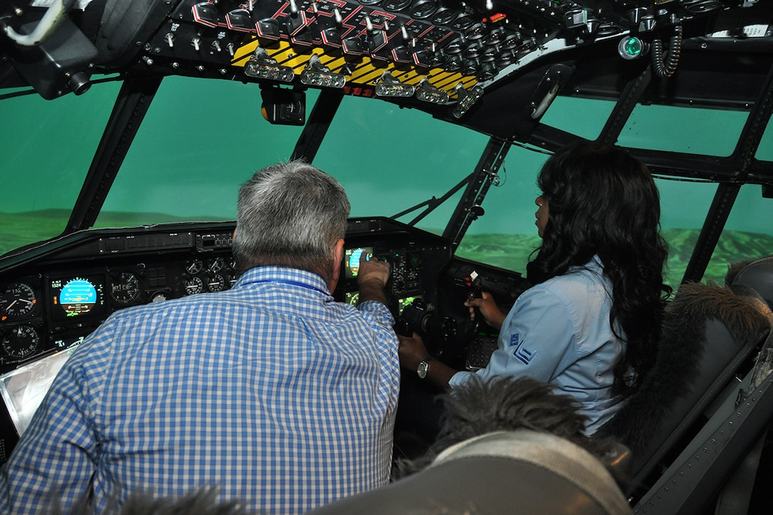 """Rob Light, simulator instructor, assists Latisha Brinson, honorary commander and Lockheed Martin Aeronautics Company Marietta site lead and senior manager ethics and business conduct, with a landing in the Eastern Regional Simulator at Dobbins Air Reserve Base, Georgia May 25, 2017. Over 40 members of the Honorary Commanders Association Class of 2017 explored various missions and training facilities at the base during their annual """"Dobbins Day."""" (U.S. Air Force photo/James Branch)"""