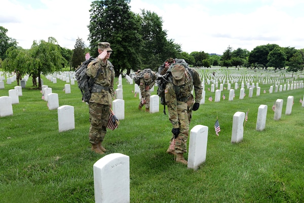 "Army Pvt. Gabriel Thyfault, left, renders honors while Army Spc. Nayib Pagan places an American flag in front of a headstone during ""Flags In'' at Arlington National Cemetery in Arlington, Va., May 25, 2017. Thyfault and Pagan are transportation specialists assigned to the 529th Regimental Support Company, 4th Battalion, 3rd U.S. Infantry Regiment, known as ""The Old Guard."" DoD photo by Sebastian J. Sciotti Jr."