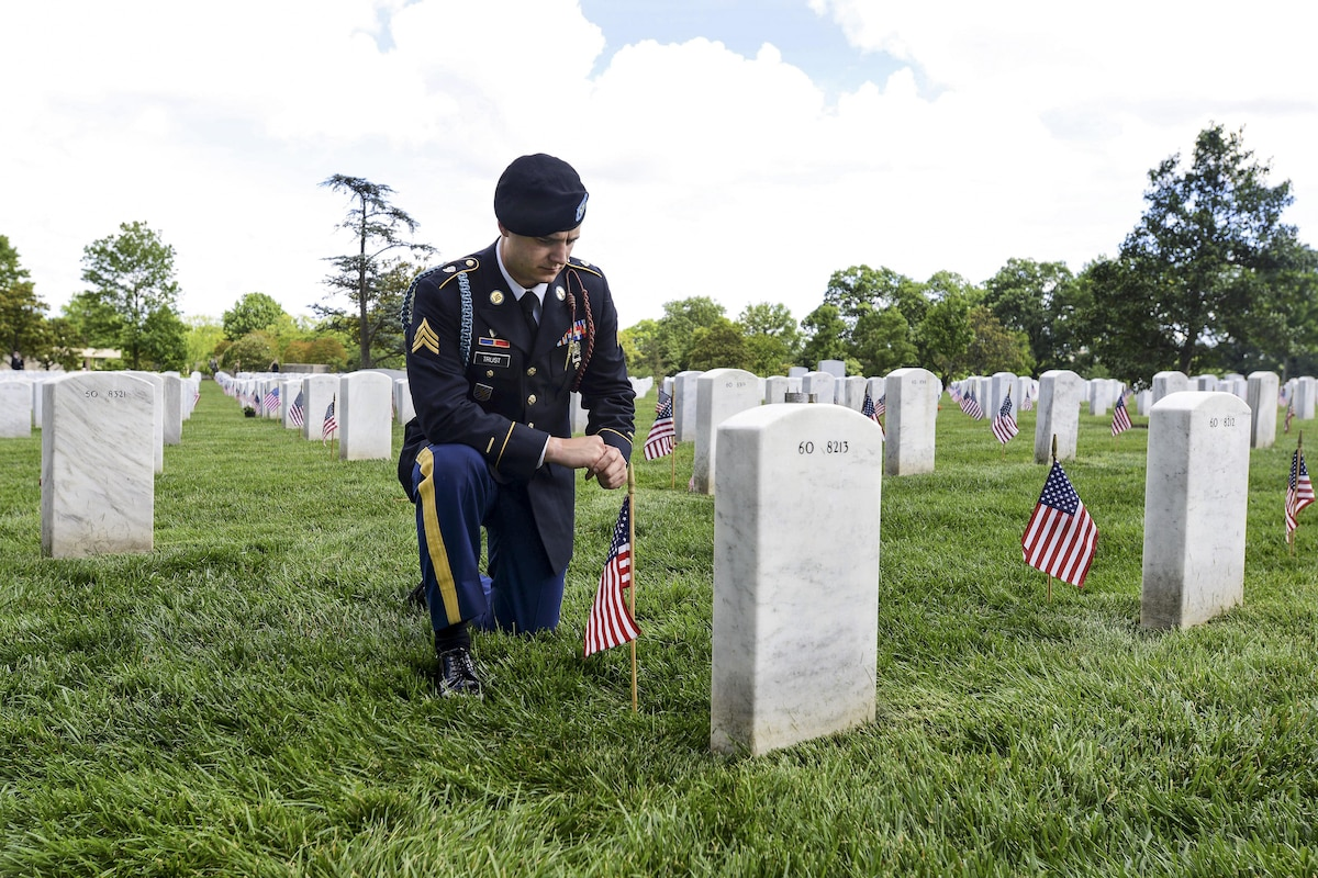 A soldier kneels as he pays respects to a close friend at a cemetery.